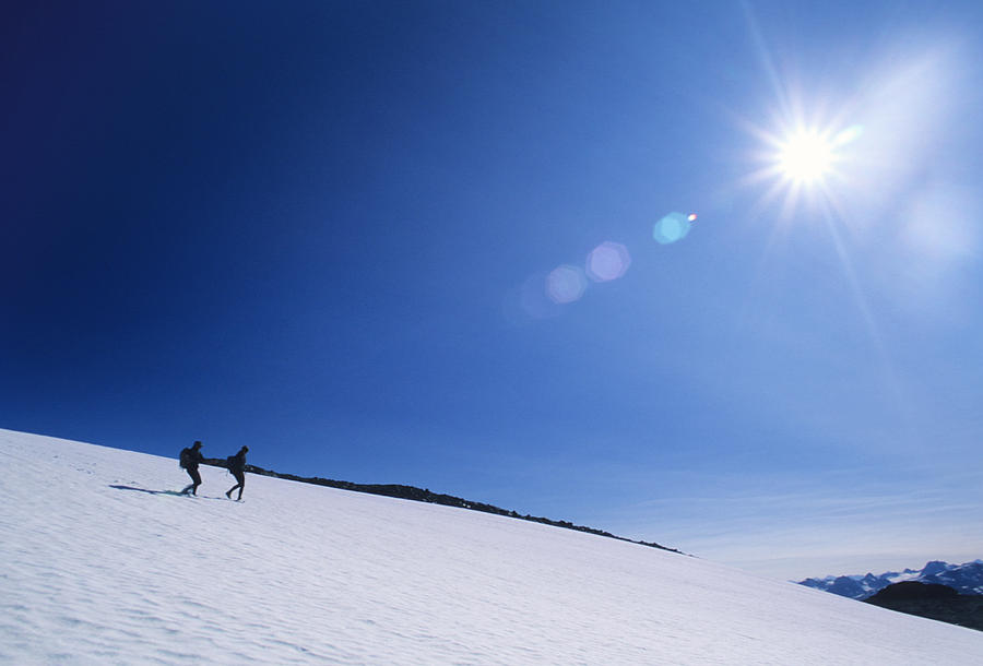 Two People Photograph - Two Hikers Explore A Snowfield by Bill Hatcher
