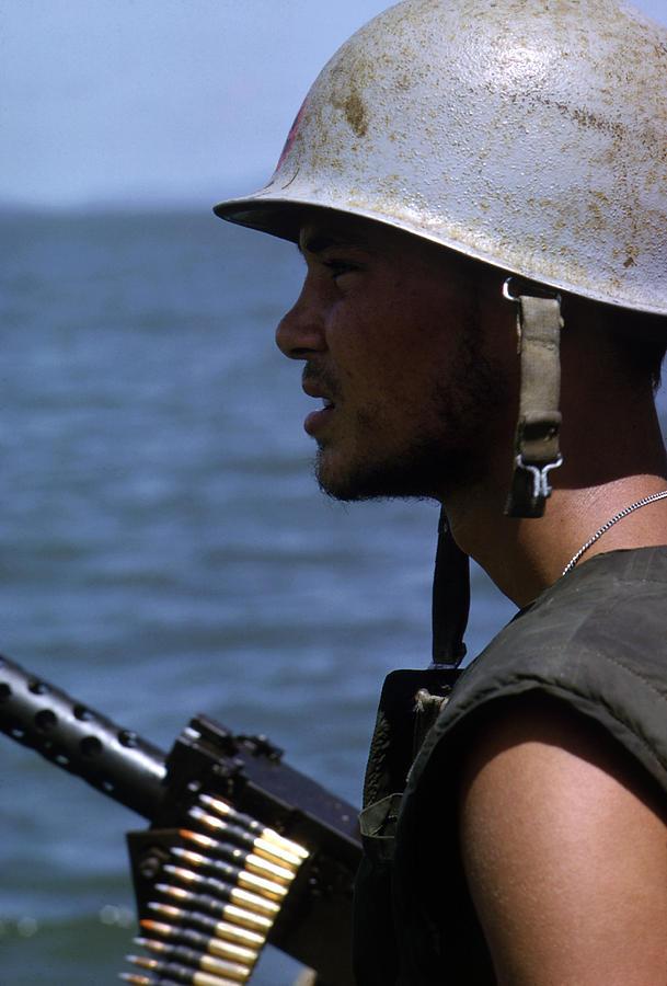 1960s Candids Photograph - Vietnam War, A Navy Gunner Mans His 50 by Everett