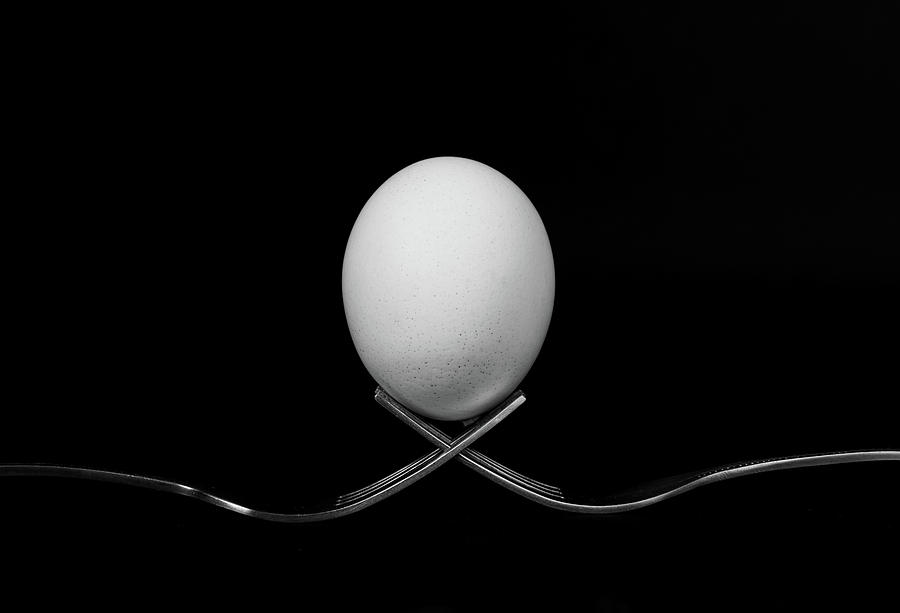 White Egg  Resting On Two Metal And Shiny Forks On A Black Backg Photograph