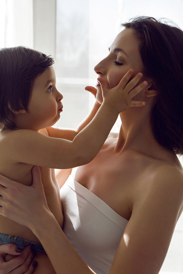 Mother In A White T-shirt Holding Her Son In Her Arms Photograph