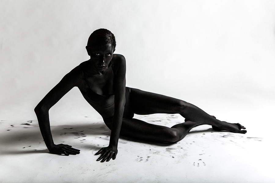 Girl Painted Black Paint Lying On A White Background Photograph