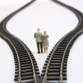 Figurines Between Two Tracks Leading Into Different Directions Symbolic Image For Making Decisions. by Bernard Jaubert