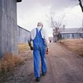 An Elderly Farmer In Overalls Walks by Joel Sartore