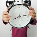 Girl Holding Alarm Clock Over Face by Sami Sarkis
