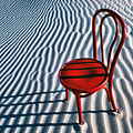 Red Chair In Sand by Garry Gay