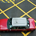 Red Taxi Cab Driving Over Yellow Lines In Hong Kong by Sami Sarkis