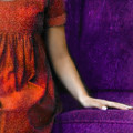 Young Woman In Red On Purple Couch by Jill Battaglia