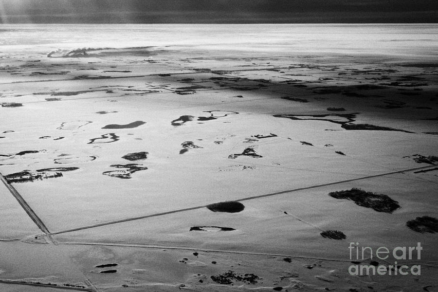 Aerial Photograph - aerial view of snow covered prairies and remote isolated farmland in Saskatchewan Canada by Joe Fox