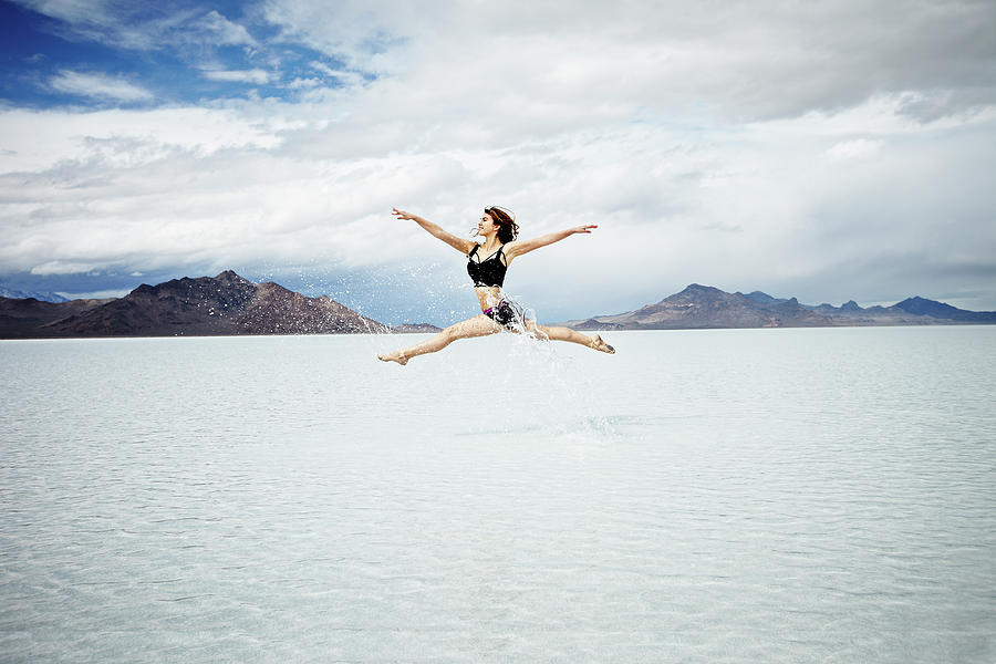 Ballerina Leaping In Mid-air Over Lake Photograph by Thomas Barwick