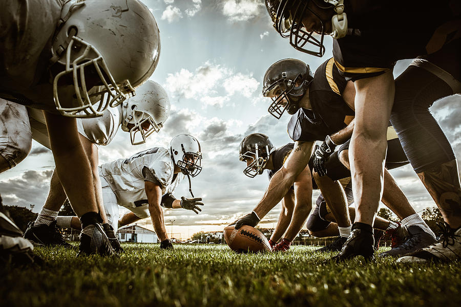 Below view of American football players on a beginning of the match. Photograph by Skynesher