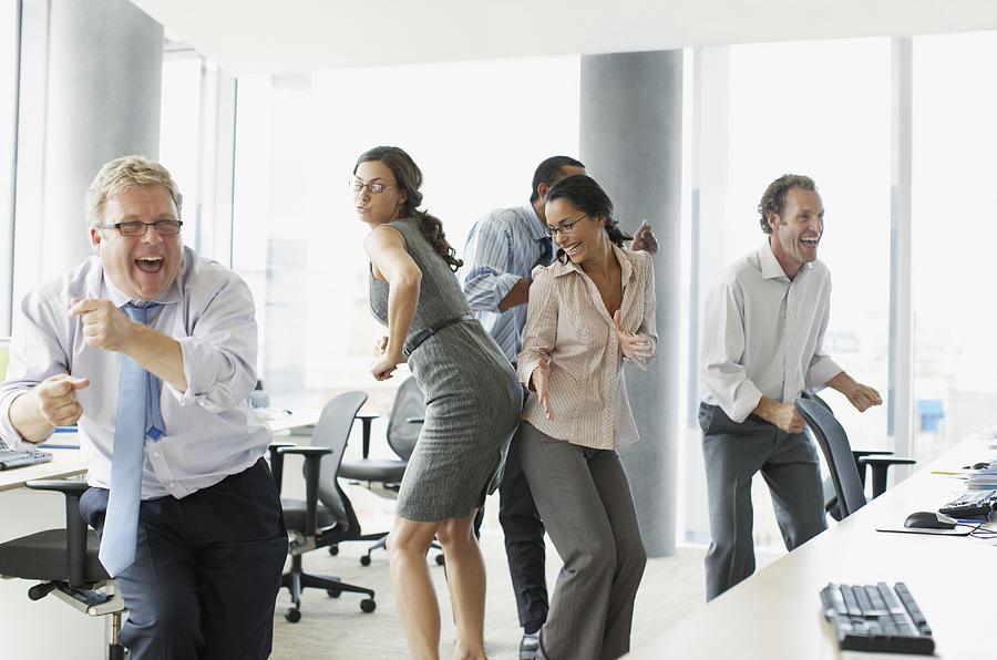 Businesspeople Dancing In Office Photograph by Paul Bradbury