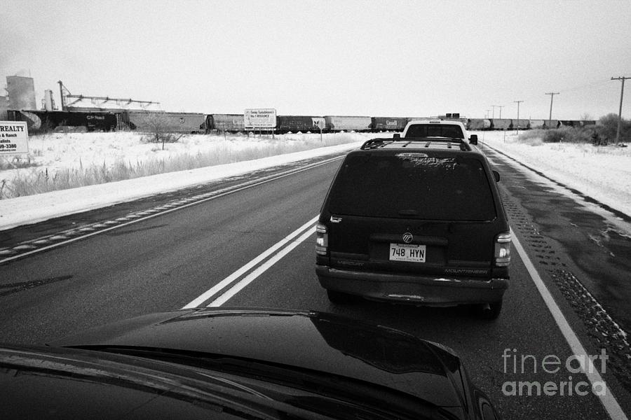 Car Photograph - cars waiting on train crossing trans-canada highway in winter outside Yorkton Saskatchewan Canada by Joe Fox