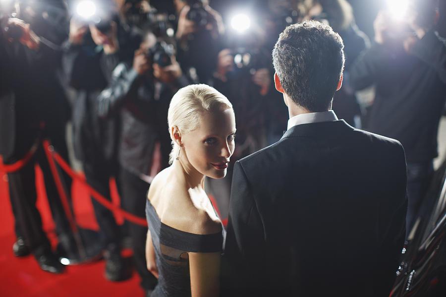 Celebrities posing for paparazzi on red carpet Photograph by Paul Bradbury