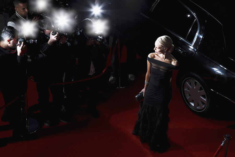 Celebrity posing for paparazzi on red carpet Photograph by Tom Merton