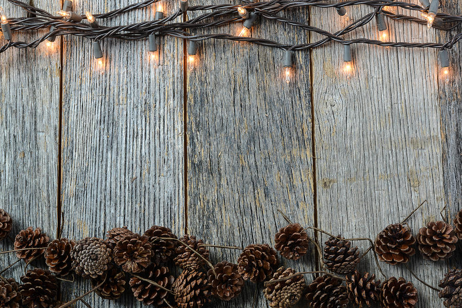Christmas Wood Background.Christmas Lights And Pinecones On Rustic Wood Background