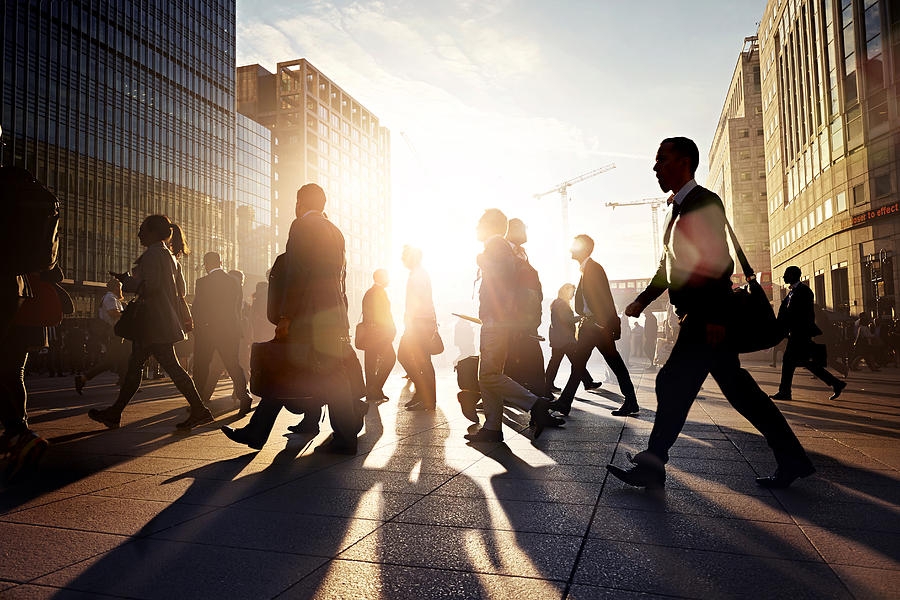 Employees walking to work in the city at sunrise Photograph by Ezra Bailey