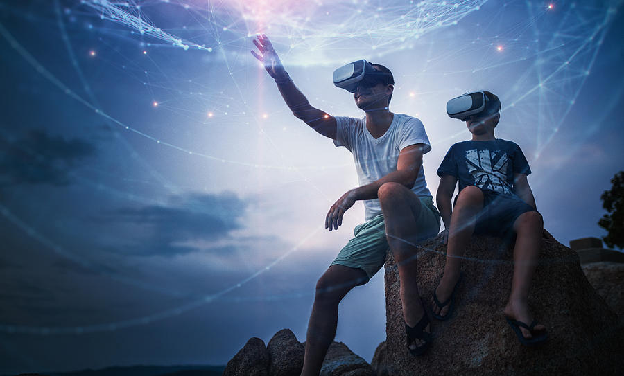 Father and son using Virtual Reality glasses sitting outside Photograph by Da-kuk