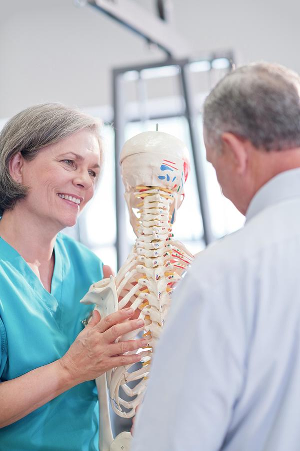 Indoors Photograph - Female Chiropractor Showing Anatomical Model by Science Photo Library