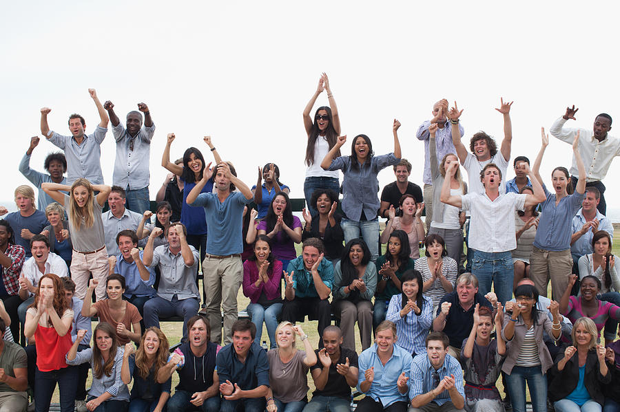 Group of spectators cheering Photograph by Martin Barraud