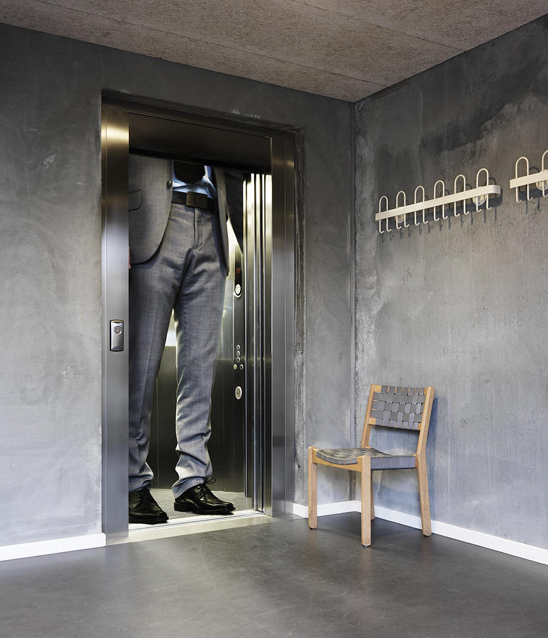 Oversized businessman in an elevator Photograph by Henrik Sorensen