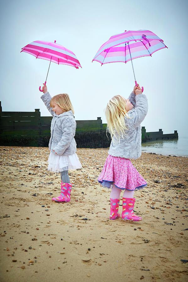 Outdoors Photograph - Two Girls On Beach Holding Umbrellas by Ruth Jenkinson