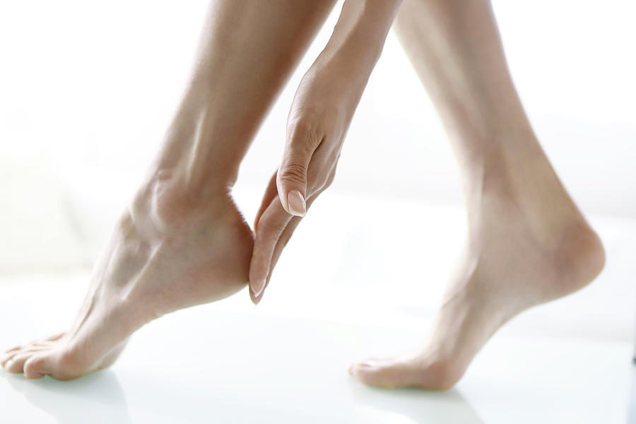 Woman Touching Feet, Low Section, Close-up Photograph by Runstudio