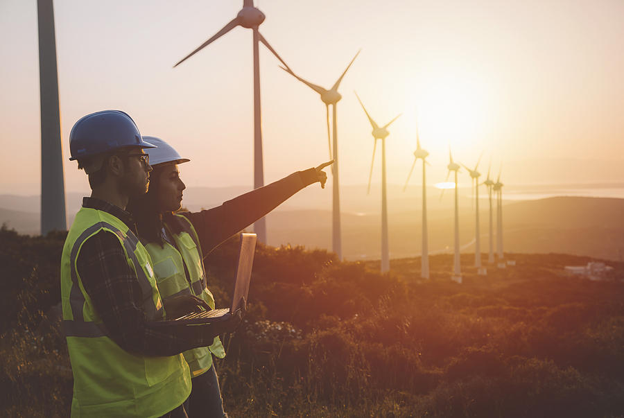 Young maintenance engineer team working in wind turbine farm at sunset Photograph by Serts