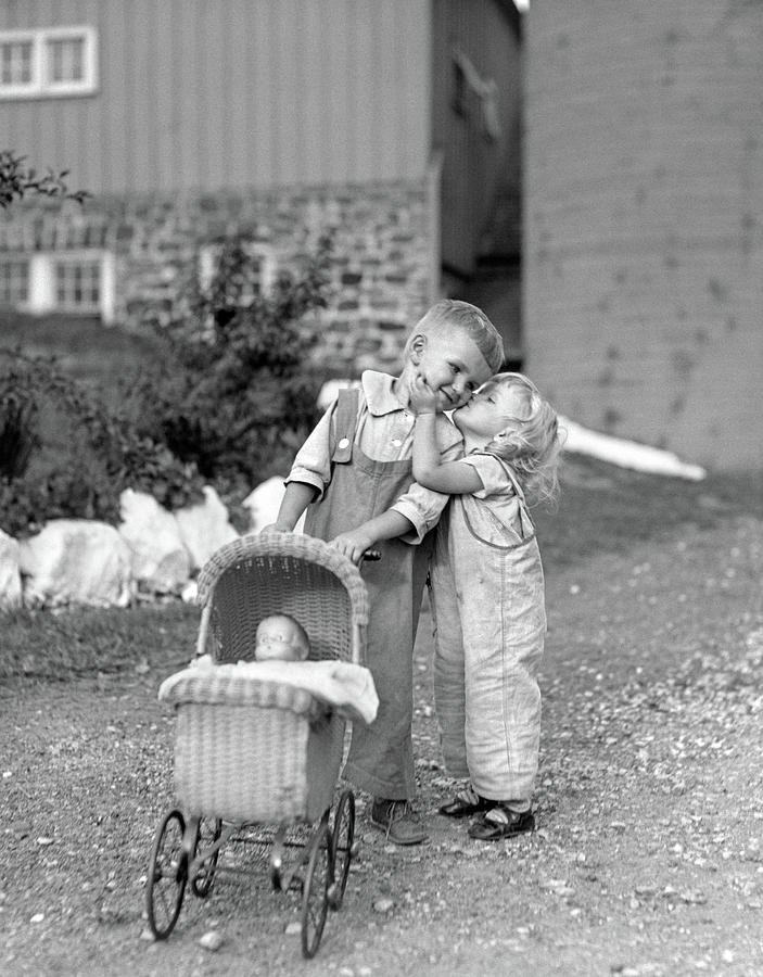 Vertical Photograph - 1930s Little Girl Kissing Boy Pushing by Vintage Images