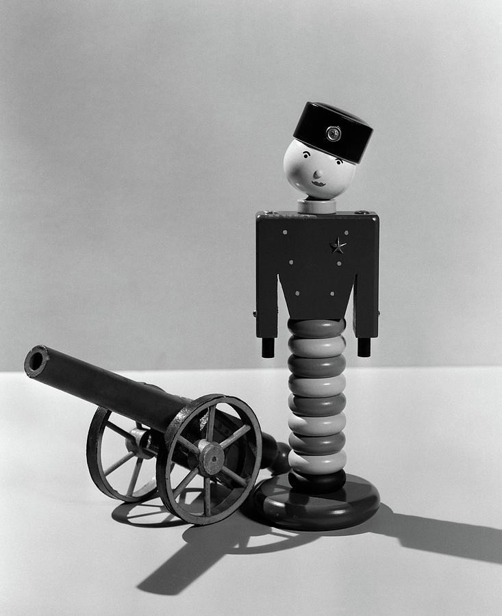 Vertical Photograph - 1930s Wooden Toy Soldier Next To Cannon by Vintage Images
