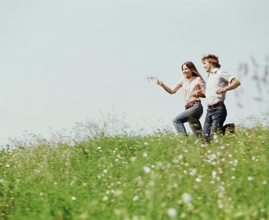 Horizontal Photograph - 1970s Boy Girl Running Field by Vintage Images