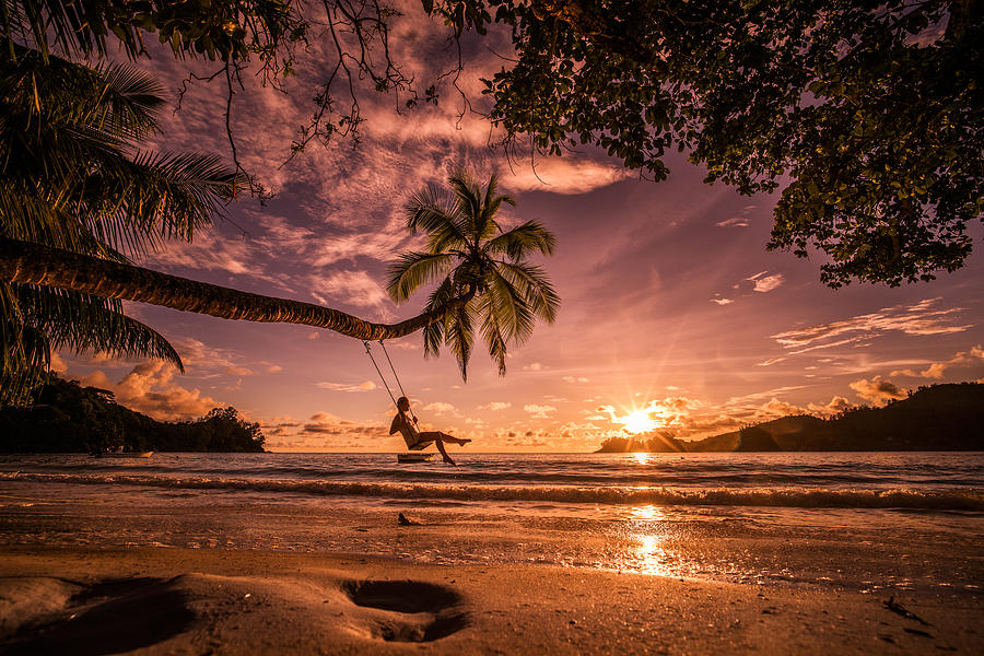 Carefree Woman Swinging Above The Sea At Sunset Beach. Photograph by BraunS