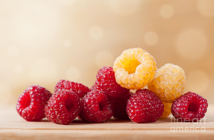 ripe red and golden raspberry fruits in pile  by Arletta Cwalina