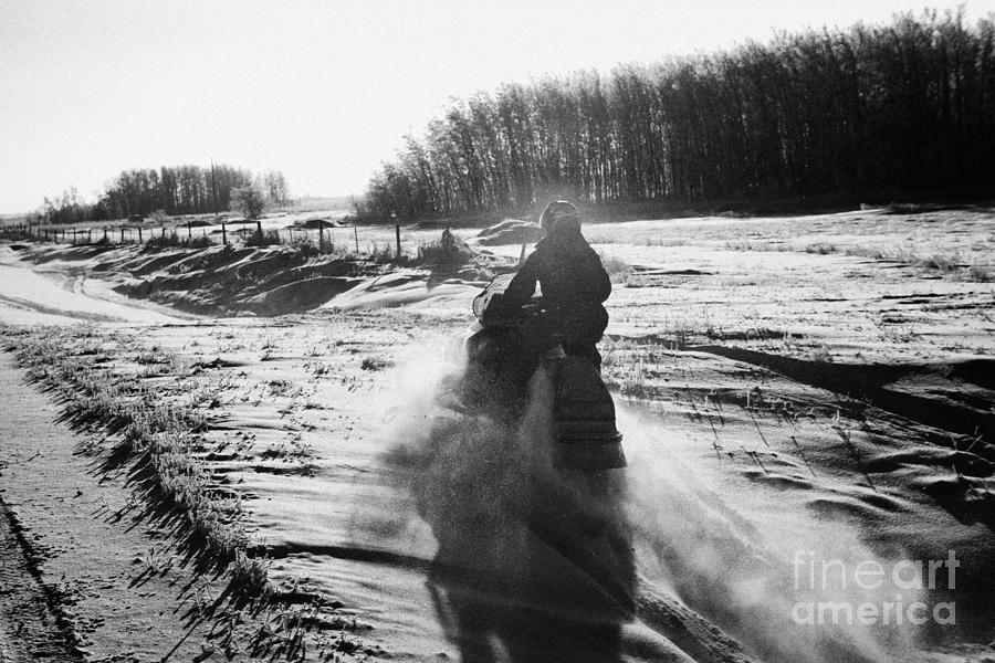 Man Photograph - man on snowmobile crossing frozen fields in rural Forget Saskatchewan Canada by Joe Fox