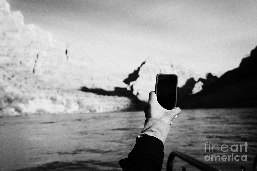 Man Photograph - man taking photos with smartphone during boat ride along the colorado river in the grand canyon Ariz by Joe Fox