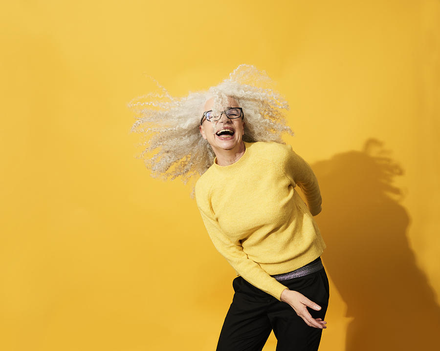 Portrait of mature woman dancing, smiling and having fun Photograph by Flashpop