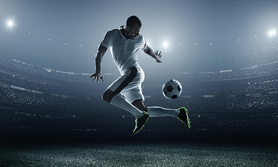 Soccer Player Kicking Ball In Stadium Photograph by Dmytro Aksonov