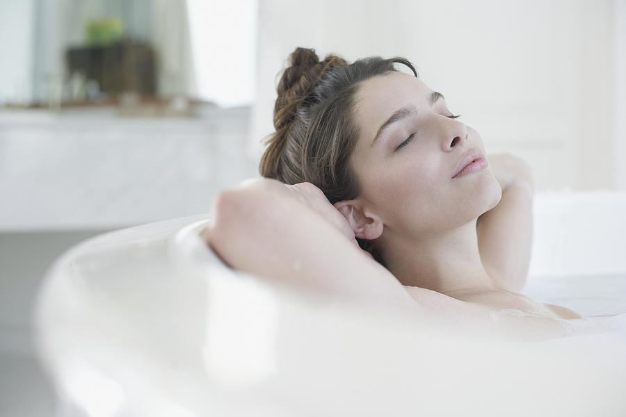 Woman relaxing in bubble bath Photograph by Sam Edwards
