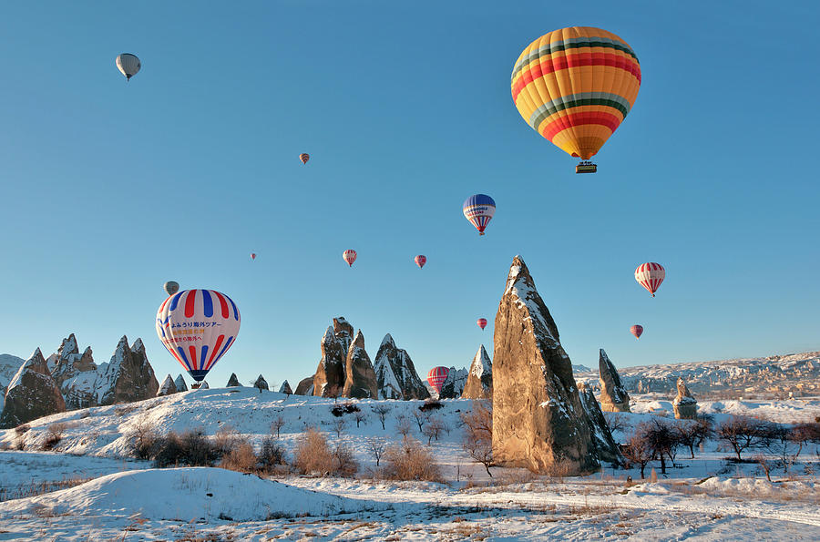 Hot Air Balloons Over Snow Covered Rock Photograph by Izzet Keribar