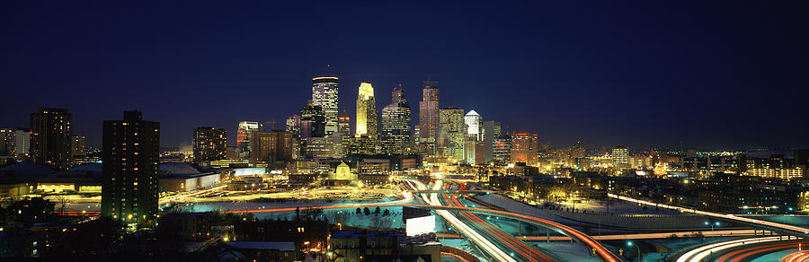 Color Image Photograph - Buildings Lit Up At Night In A City by Panoramic Images