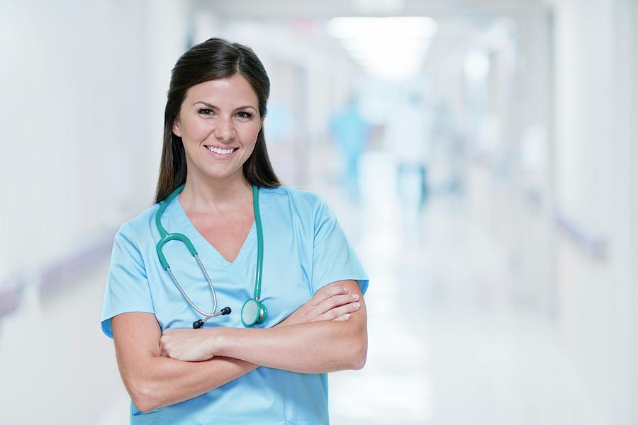 Indoors Photograph - Female Doctor Smiling Towards Camera by Science Photo Library