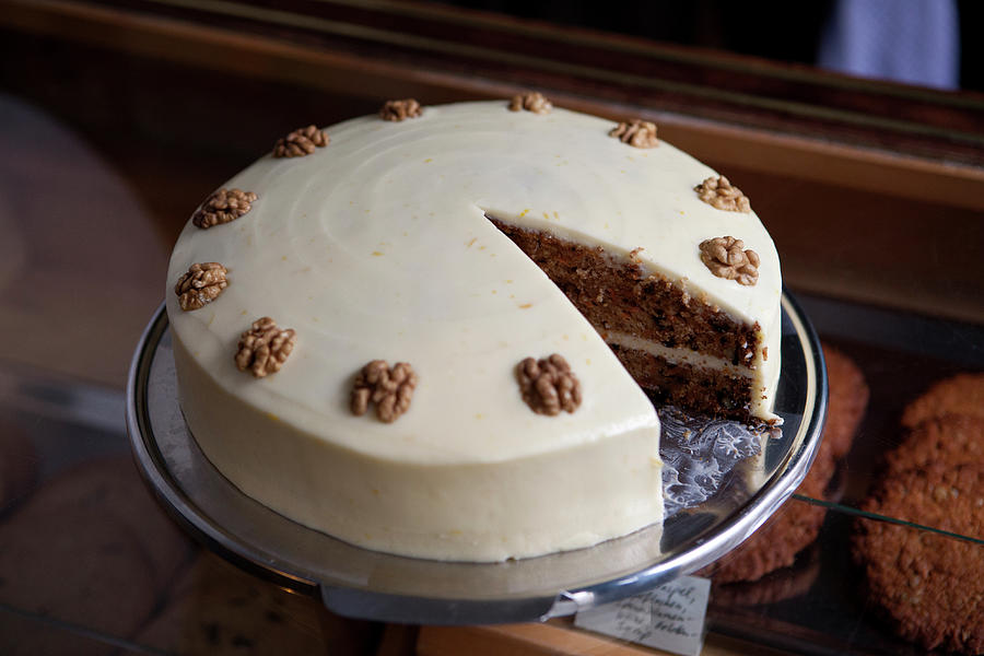 A Carrot Cake On A Display Cabinet In A Photograph by Halfdark
