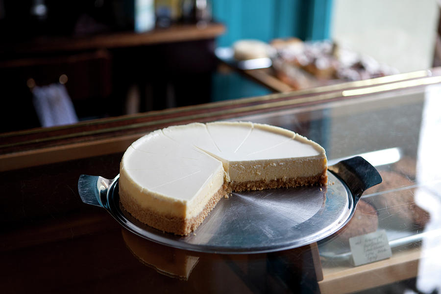 A Cheesecake Cut Into Slices On A Photograph by Halfdark