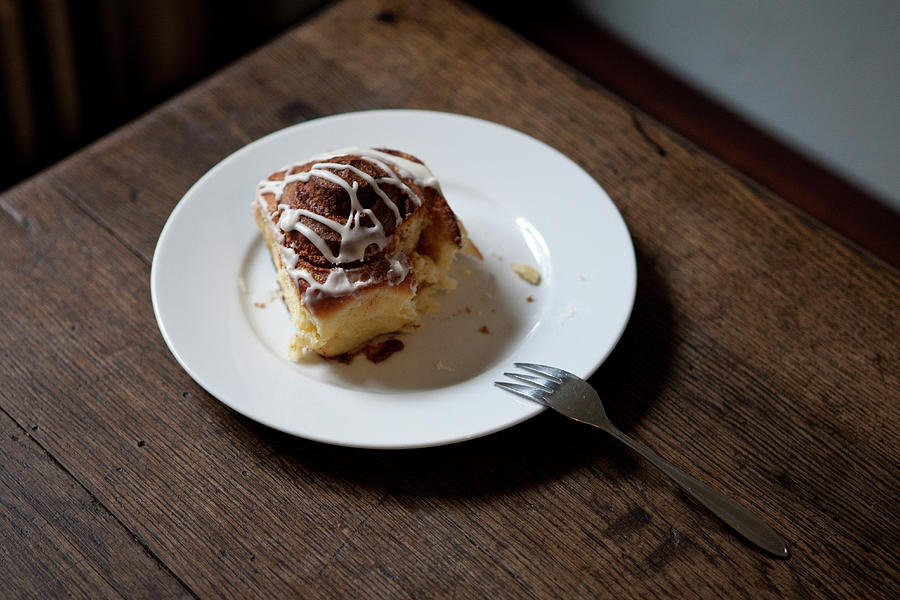 A Cinnamon Roll On A Plate With A Bite Photograph by Halfdark