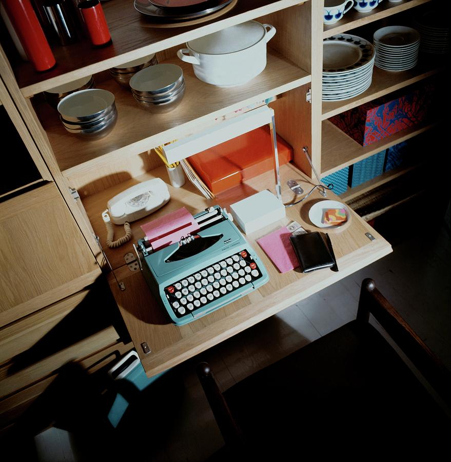 A Cupboard With A Blue Typewriter Photograph by Ernst Beadle