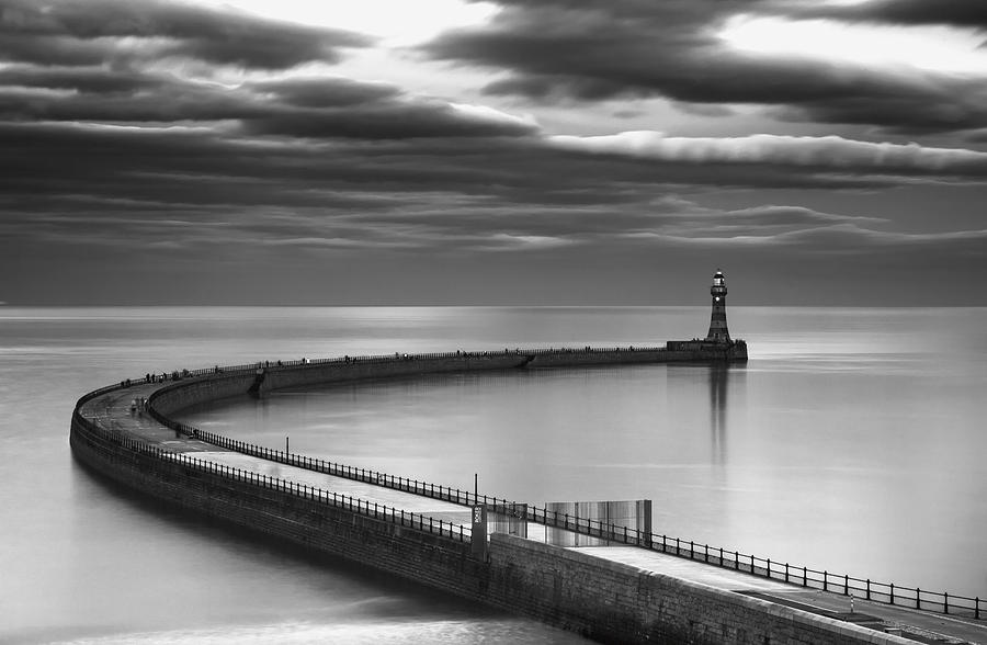Lighthouse Photograph - A Curving Pier With A Lighthouse At The by John Short