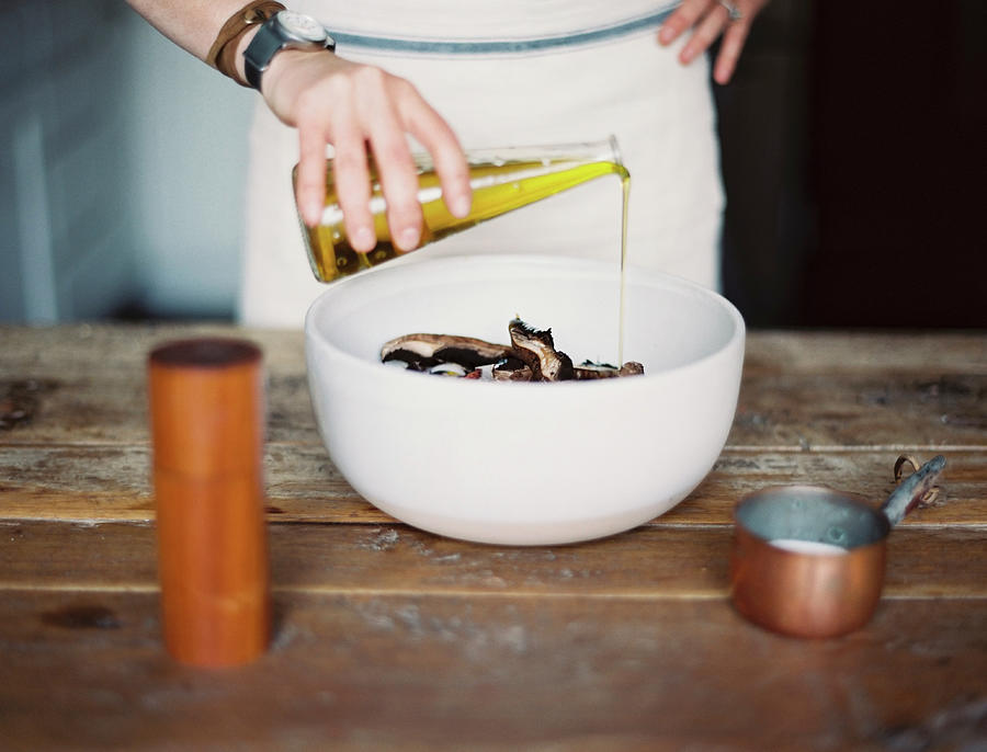 A Domestic Kitchen. A Woman Wearing An Photograph by Mint Images - Britt Chudleigh