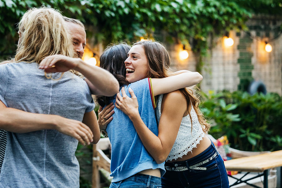 A Group Of Friends Embrace, Excited To See Each Other At Barbecue Meetup Photograph by Hinterhaus Productions