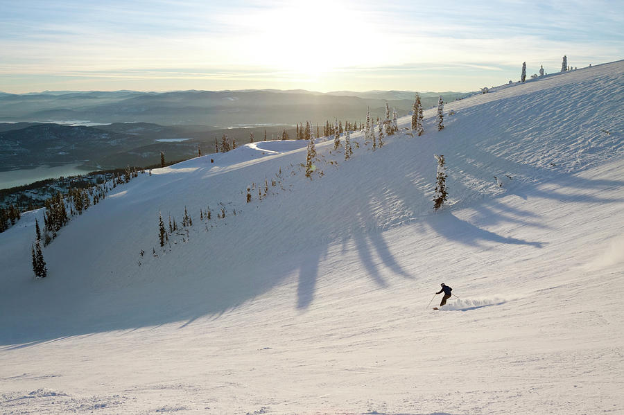 Extreme Sports Photograph - A Lone Skier Makes A Turn At Whitefish by Craig Moore