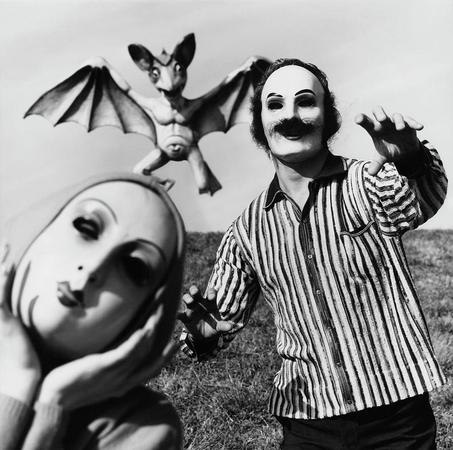 A Man And Woman Wearing Masks With A Bat Flying Photograph by Chadwick Hall