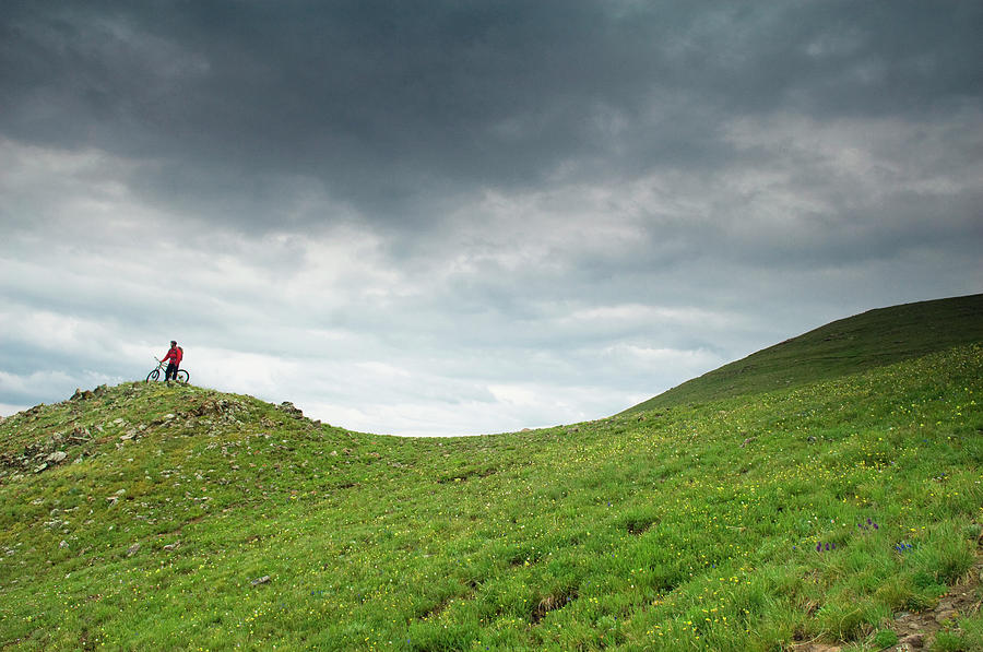 Bicycle Photograph - A Man Sitting On Top Of A Tundra Ridge by Keith Ladzinski